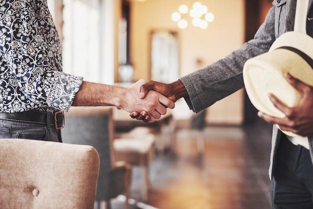 Empresários de preto e branco, apertando as mãos