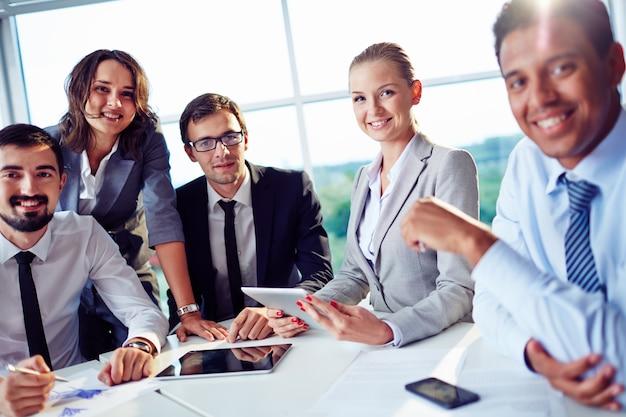 Empresários de sorriso que têm uma reunião de negócios