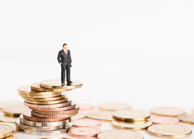 Empresários de sucesso em miniatura ficam em cima de moedas de ouro isoladas no fundo branco, conceito de alto risco alto retorno