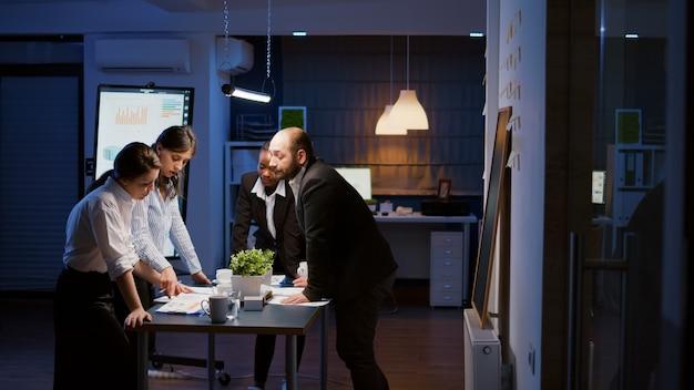 Empresários de várias etnias apoiam-se na mesa de conferência, analisando as ideias de estratégia da empresa que sobrecarregam na apresentação da gestão. solução financeira de brainstorming de trabalho em equipe diversa na sala de reuniões