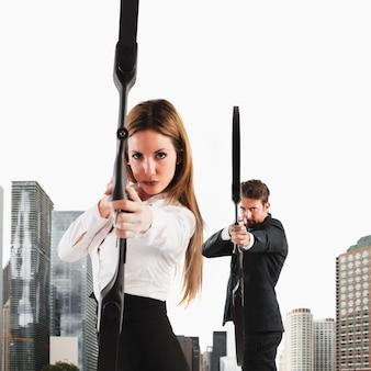 Empresários determinados com arco e flecha mirando um alvo