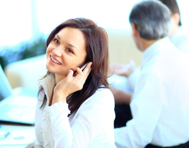 Empresários discutem o negócio em segundo plano enquanto a mulher atende