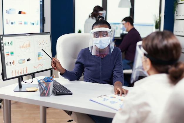 Empresários discutindo as tabelas e gráficos que mostram seu sucesso. equipe multiétnica trabalhando em empresa com nova normalidade respeitando a distância social por causa da pandemia global com coronavírus.