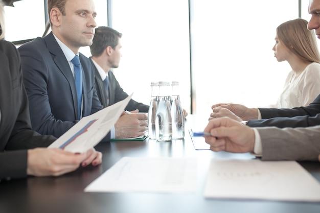 Empresários discutindo documentos no local de trabalho, no escritório, sentados ao redor da mesa
