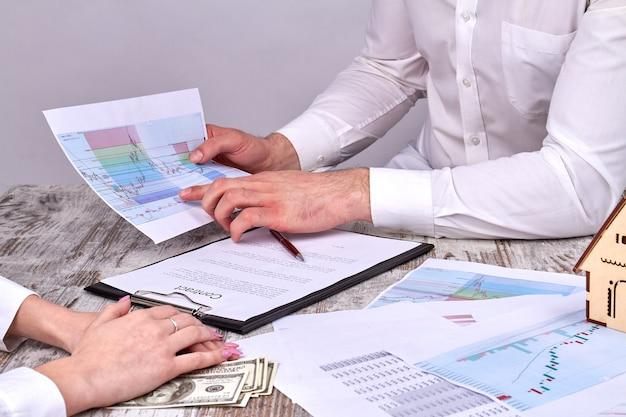 Empresários discutindo gráficos estatísticos gráficos estatísticos antes de assinarem o contrato