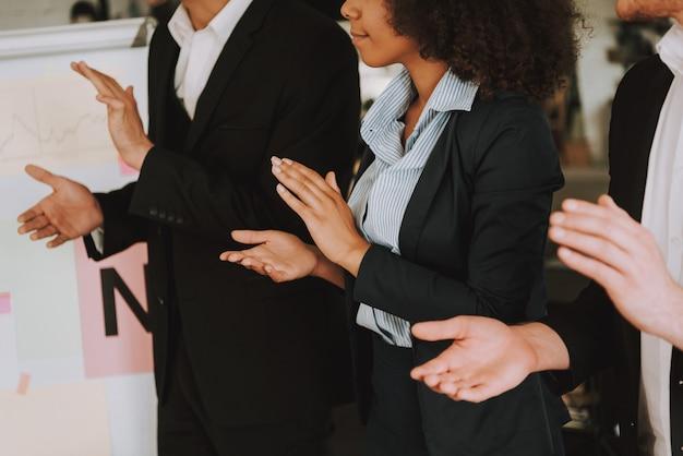 Empresários e empresária é palmas de mãos.