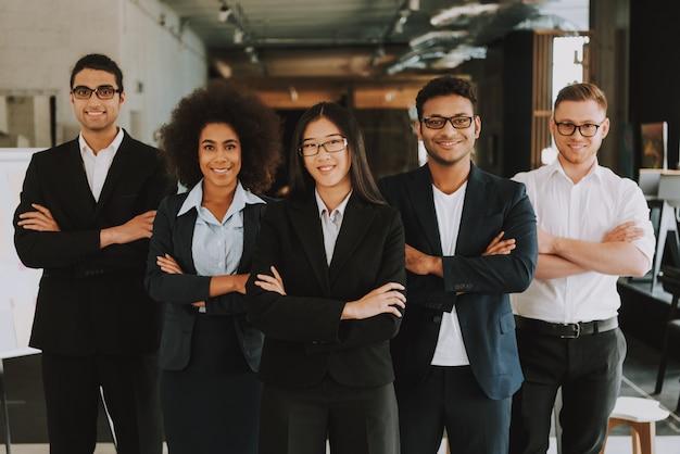 Empresários e empresárias com braços cruzados está sorrindo.