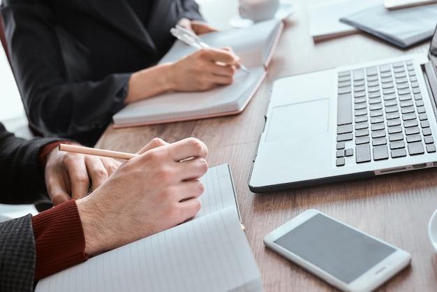 Empresários e mulher de negócios no escritório trabalhando sentados à mesa juntos, fazendo anotações em planejadores em close-up de reunião de negócios
