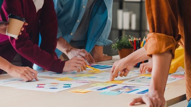 Empresários e mulheres de negócios asiáticos se reunindo para debater ideias sobre o aplicativo de planejamento de web design criativo e desenvolver um layout de modelo para projeto de telefone celular trabalhando juntos em um pequeno escritório.