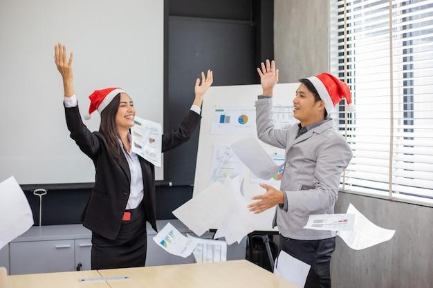 Empresários e mulheres de negócios asiáticos sucesso e equipe feliz em ganhar com as mãos levantadas, comemorando o avanço e as conquistas