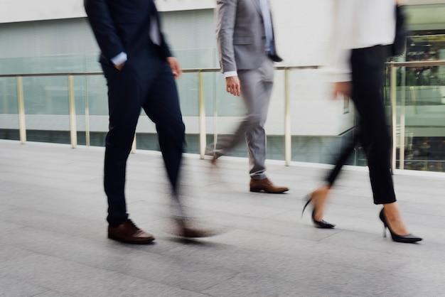 Empresários e uma empresária em terno andando em uma cidade na hora do rush