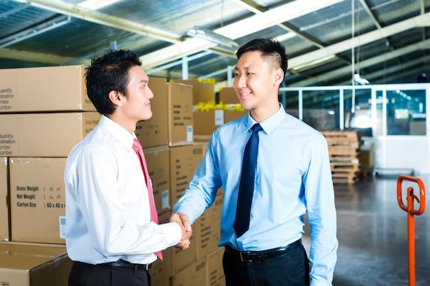 Empresários em armazém têm um acordo