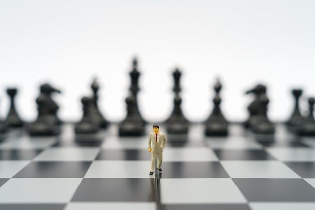 Empresários em miniatura 2 pessoas em pé em um tabuleiro de xadrez com uma peça de xadrez