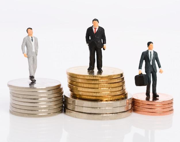 Empresários em miniatura apoiam-se em moedas de dinheiro isoladas em branco, conceito de vencedor de competição empresarial
