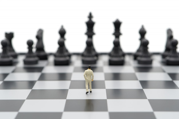 Empresários em miniatura, de pé sobre um tabuleiro de xadrez com uma peça de xadrez nas costas.