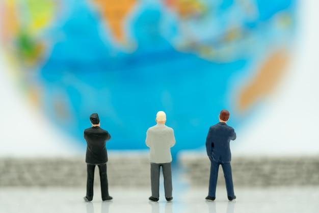 Empresários em miniatura e o globo