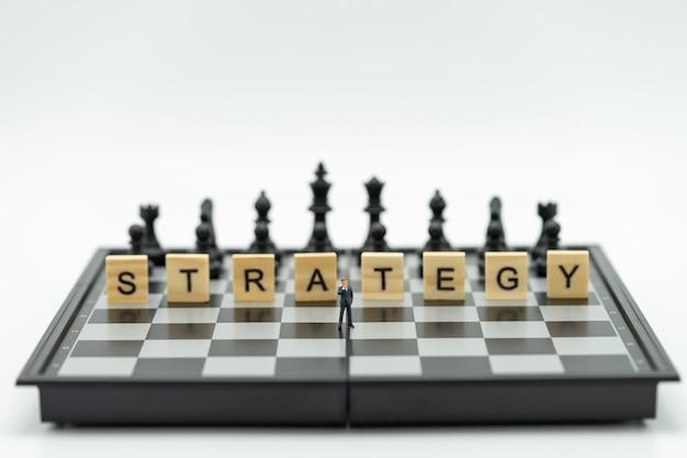 Empresários em miniatura em pé em um tabuleiro de xadrez com uma peça de xadrez