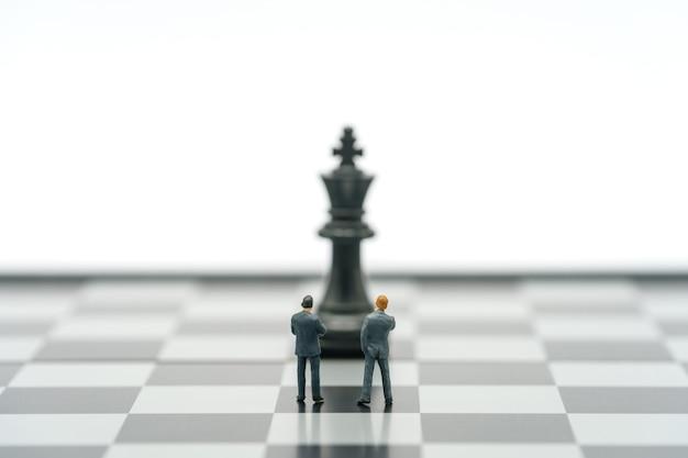 Empresários em miniatura em um tabuleiro de xadrez com uma peça de xadrez nas costas.