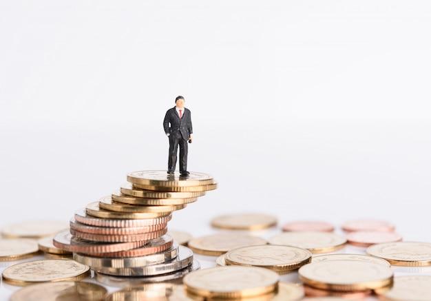 Empresários em miniatura se apoiam em moedas de dinheiro isoladas em branco, conceito de sucesso empresarial