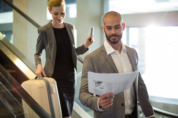 Empresários em pé na escada rolante com bagagem