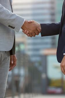 Empresários em pé na rua da cidade e apertando as mãos