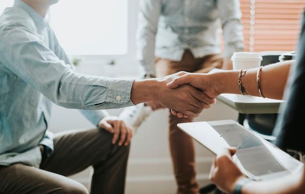 Empresários em reunião apertando as mãos