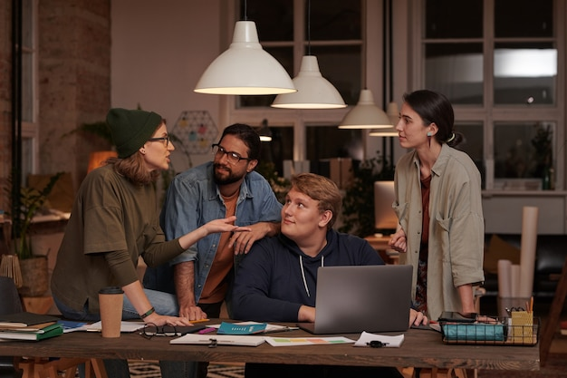Empresários em roupas casuais discutindo juntos uma apresentação on-line no laptop, trabalhando em equipe
