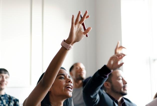 Empresários em seminário levantando as mãos