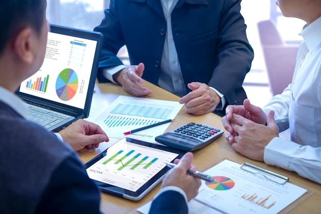 Empresários em uma reunião com uma mesa cheia de documentos com estatísticas