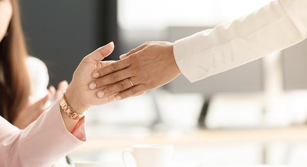 Empresários entrando no escritório passaram por fileiras de empresárias sentadas, batendo palmas e dando high-five, toque na palma da mão com todos. ideia para emoção feliz com sucesso e querido trabalho em equipe.
