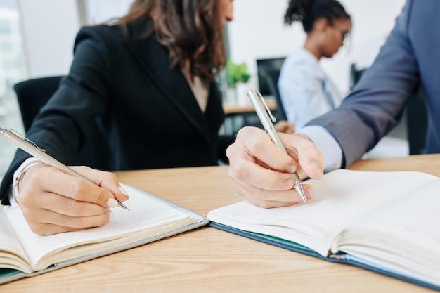 Empresários escrevendo em planejadores