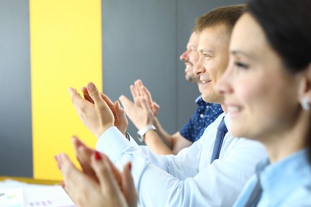 Empresários estão aplaudindo e olhando para longe