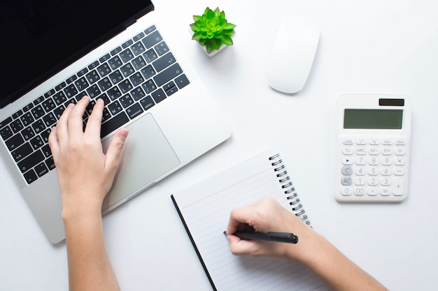 Empresários estão tomando notas e usando laptops em uma mesa branca. conceito de contabilidade, vista superior.