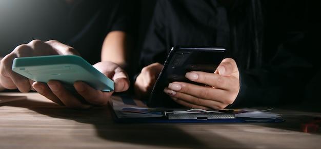 Empresários estão usando telefone celular e calculadora na mesa de trabalho