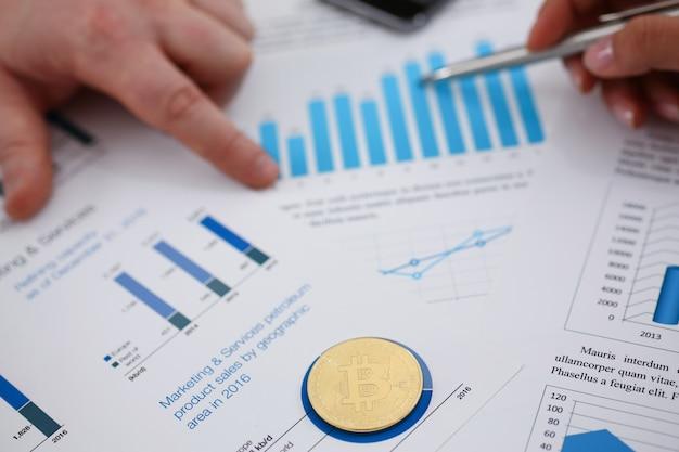 Empresários estudam documentos closeup de moeda digital