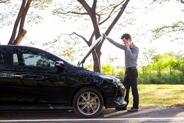 Empresários falando no celular por causa de carro quebrado