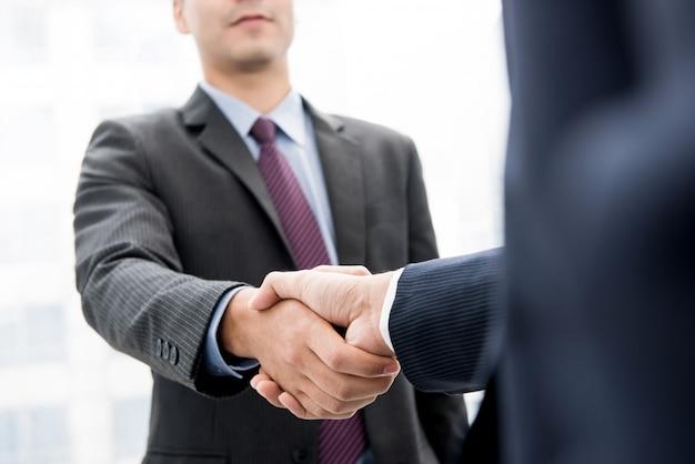 Empresários fazendo aperto de mão - conceitos de saudação, negociação, fusão e aquisição