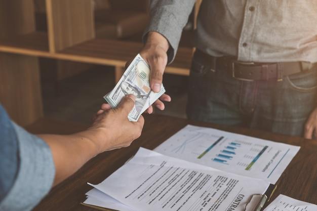 Empresários, fazendo o aperto de mão com o dinheiro nas mãos, conceitos de corrupção e suborno.