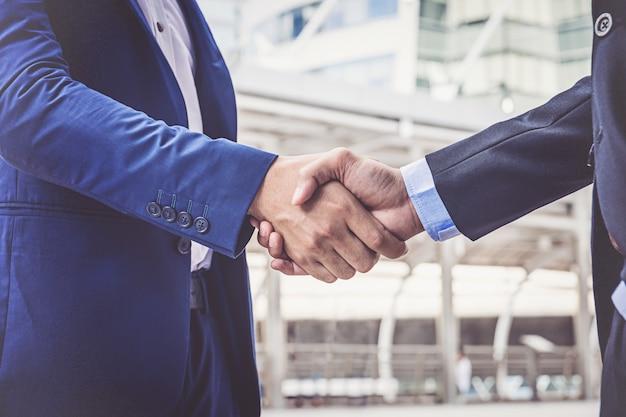 Empresários fazendo o aperto de mão. empresários bem sucedidos de conceito