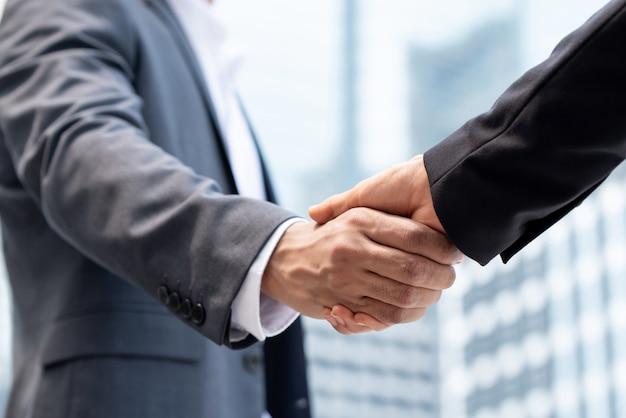 Empresários fazendo o aperto de mão na cidade