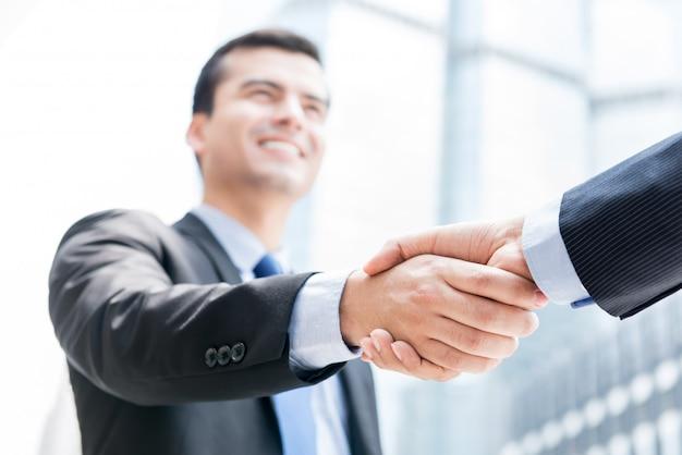 Empresários fazendo o aperto de mão na frente de prédios de escritórios na cidade