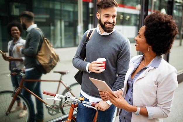 Empresários felizes discutindo e sorrindo enquanto caminham juntos ao ar livre
