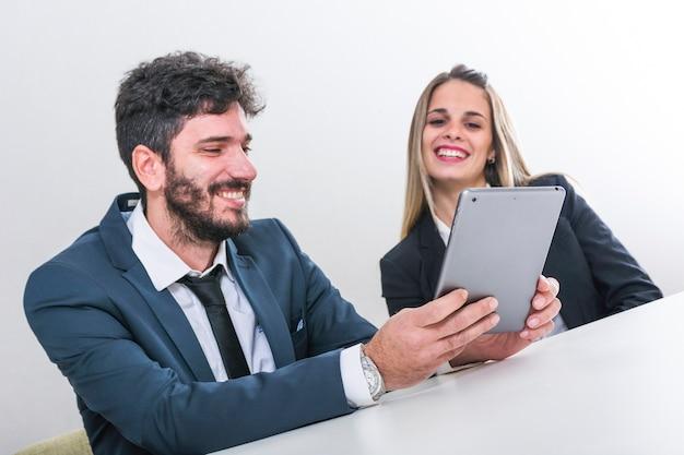 Empresários felizes olhando para tablet digital