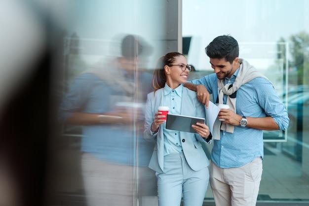 Empresários felizes usando o tablet para ler e-mails em pé ao ar livre e beber café.