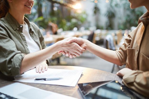 Empresários femininos, apertando as mãos na reunião