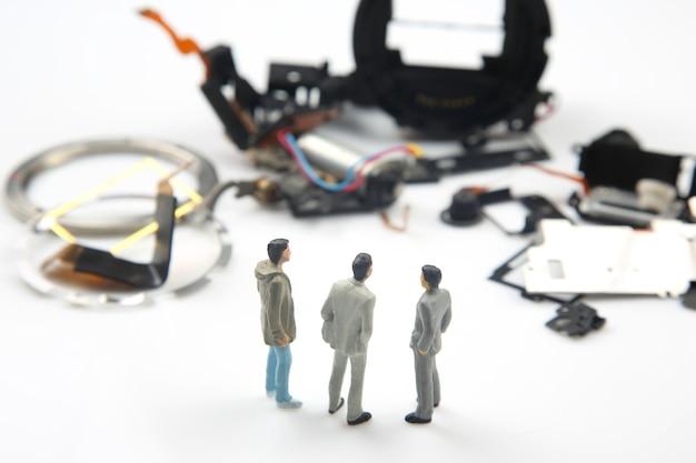 Empresários ficam perto de peças desmontadas de um dispositivo eletrônico