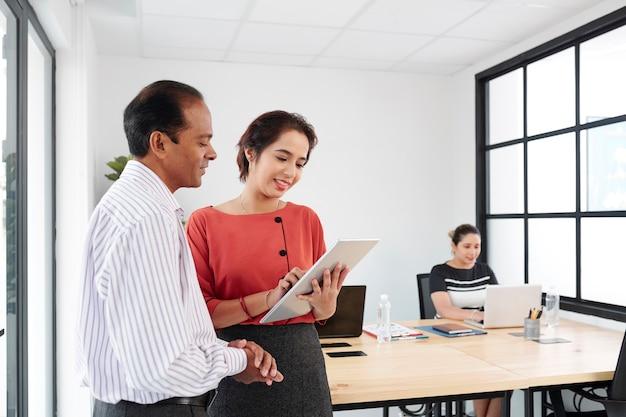 Empresários indianos sorridentes discutindo um documento em um tablet digital e seus colegas trabalhando em um laptop