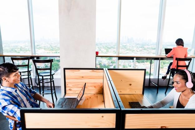 Empresários iniciantes em escritório de coworking trabalhando em cubículos