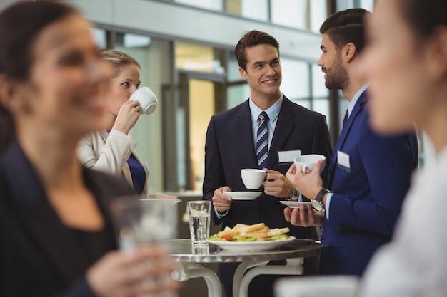 Empresários interagindo entre si enquanto tomam café