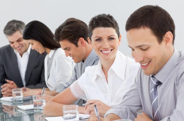 Empresários internacionais que tomam notas em uma reunião
